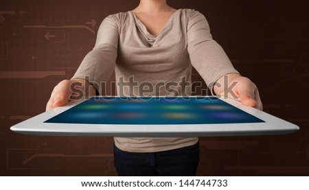 Young woman holding a white tablet with blurry apps - stock photo