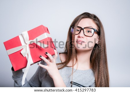 young woman holding a wrapped gift, closeup isolated on gray - stock photo