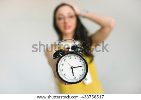 Young woman holding alarm clock and her head horrified about deadlines - stock photo