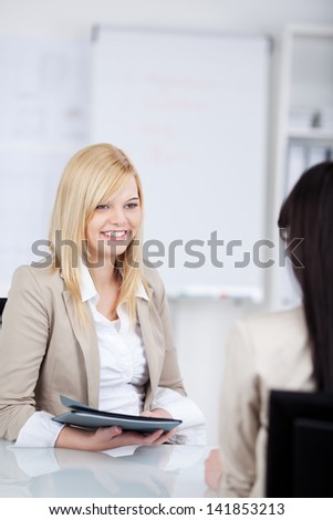 young woman holding an application folder in an interview in the office - stock photo