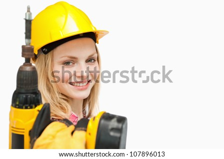 Young woman holding an electric screwdriver against white background - stock photo