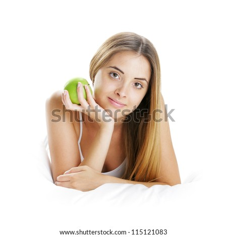 Young Woman Holding Apple in Bed - stock photo