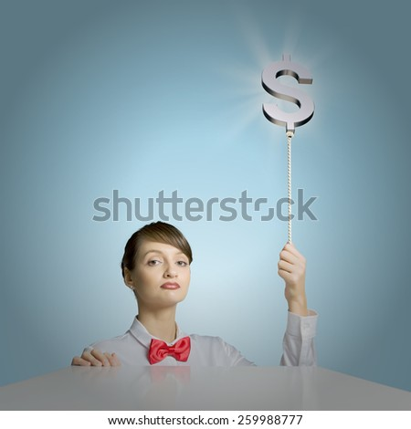Young woman holding balloon shaped like dollar sign - stock photo