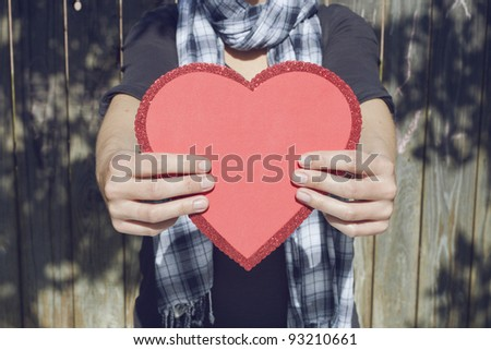 Young woman holding big red heart in her hands, copy space - stock photo