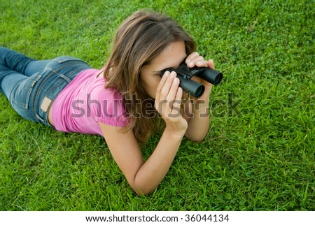Young woman holding binocular lenses on grass - stock photo