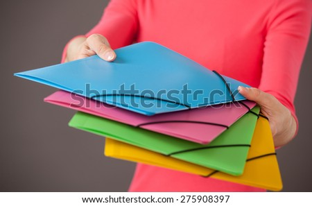 Young woman holding bright folders, gray background - stock photo