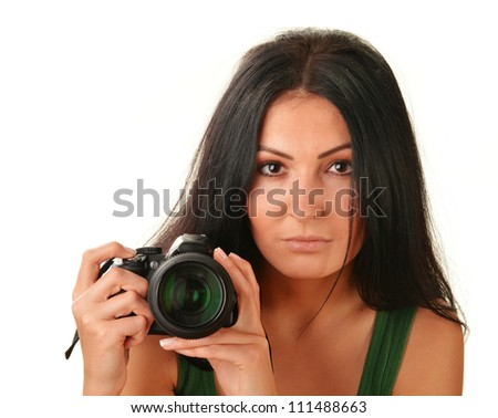 Young woman holding camera isolated on white. Taking pictures. - stock photo