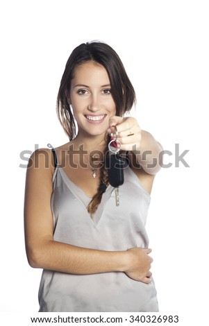 Young woman holding car key isolated on white background - stock photo