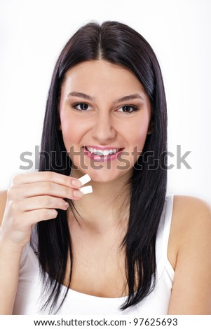 young woman holding chewing gums in her hand. - stock photo