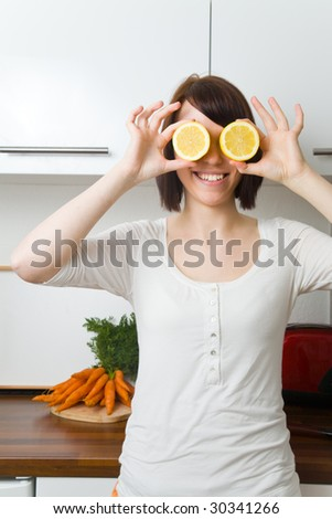 Young woman holding citrons in front of her eyes - stock photo