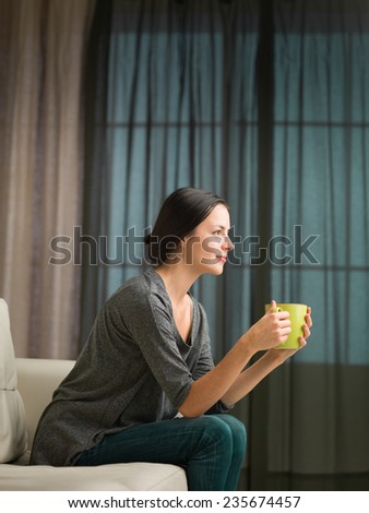 young woman holding coffee mug on couch daydreaming at home - stock photo