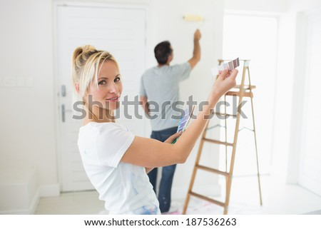Young woman holding color swatches with man by ladder in a new house - stock photo
