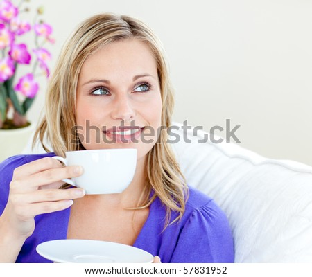 Young woman holding cup against white background - stock photo