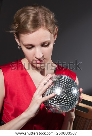 Young woman holding disco ball on grey background - stock photo