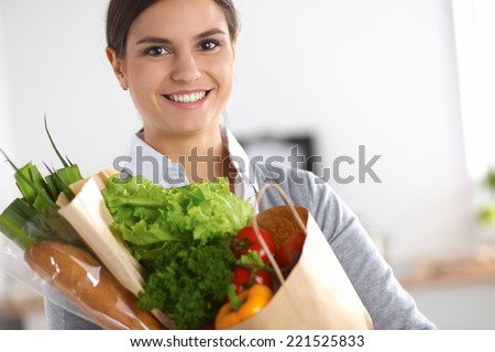 Young woman holding grocery shopping bag with vegetables Standi - stock photo