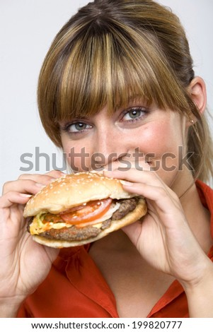 Young woman holding hamburger, portrait, close-up - stock photo