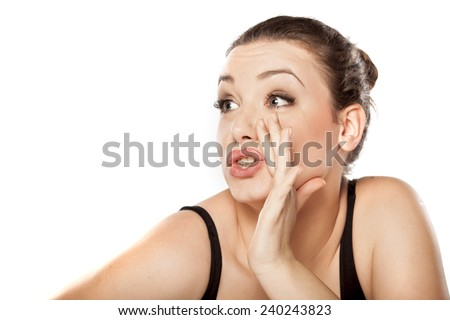 young woman holding hand next to her mouth and whispers - stock photo