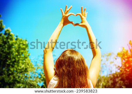 Young woman holding hands in heart shape framing on sky background - stock photo
