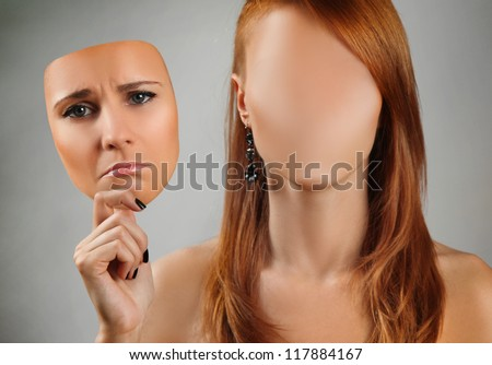 young woman holding happy mask - stock photo