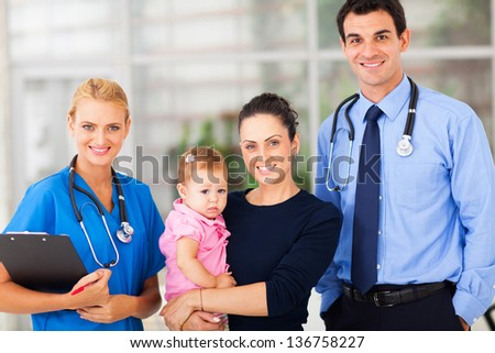 young woman holding her baby standing with doctor and female nurse in hospital - stock photo