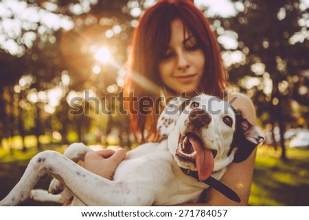 Young woman holding her dog in nature  - stock photo