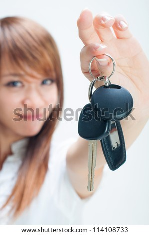 Young woman holding her first own car key on white background, focus on car key. - stock photo
