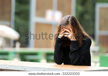 Young woman holding her head in shame. - stock photo