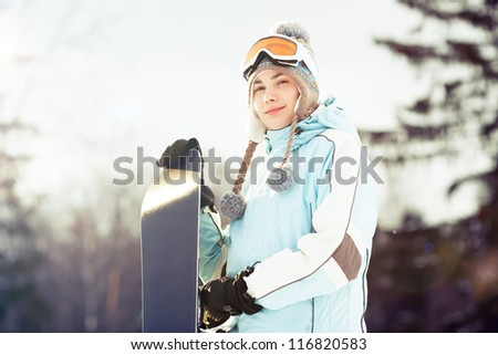 Young woman holding her snowboard, she's looking away and smiling, copy space, close up, lens flare - stock photo