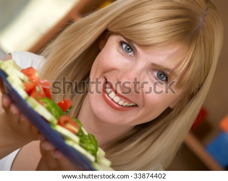 young woman holding in her hand a bowl of salad - stock photo