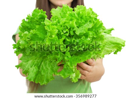 Young woman holding lettuce, green salad over white background - stock photo