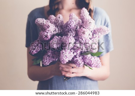 Young woman holding lilac flowers - stock photo