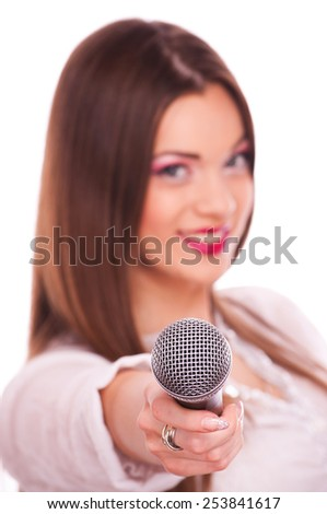 Young woman holding microphone, on white background with focus on the microphone - stock photo