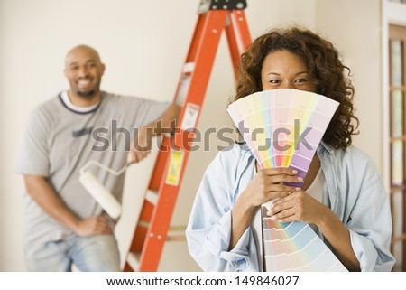 Young woman holding paint swatches - stock photo