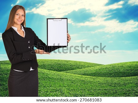 Young woman holding paper holder with nature on background. Green feild and blue sky - stock photo