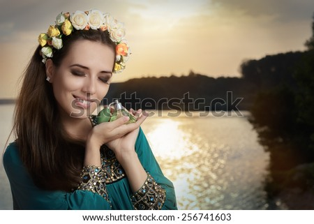 Young Woman Holding Perfume Bottle at Sunset - Portrait of a glamorous woman with retro fragrance recipient in seaside landscape  - stock photo