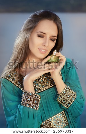 Young Woman Holding Perfume Bottle in Seaside Landscape - Portrait of a glamorous woman with retro fragrance recipient in beautiful seascape  - stock photo
