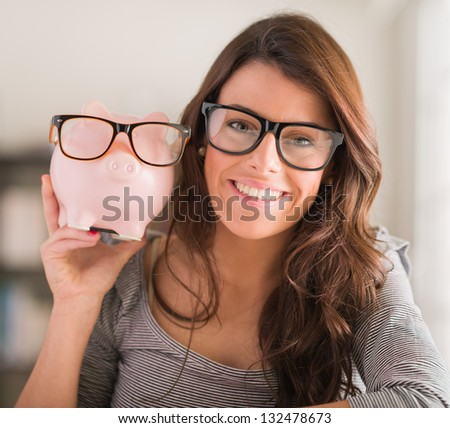 Young Woman Holding Piggy Bank Wearing Glasses, Indoors - stock photo
