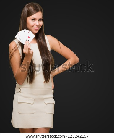 Young Woman Holding Playing Cards against a black background - stock photo