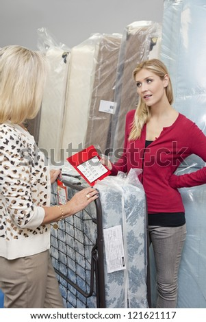 Young woman holding price list while looking at mother in furniture store - stock photo
