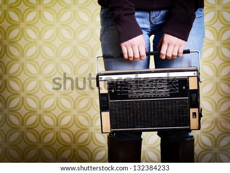 young woman holding radio player in room with vintage wallpaper, detail, retro stylization 60-70s, toned - stock photo