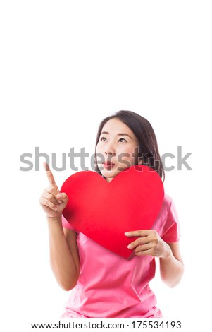 Young woman holding red heart and pointing up on white background - stock photo
