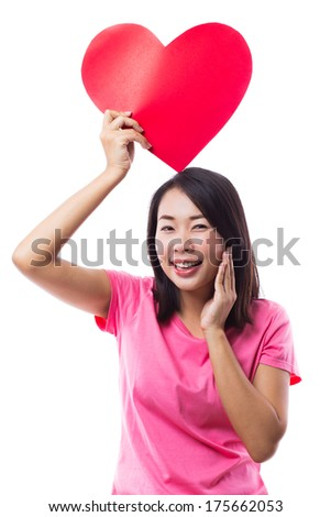 Young woman holding red heart over head on white background - stock photo