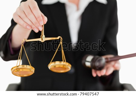 Young woman holding scales of justice and a gavel with the camera focus on the scales against a white background - stock photo