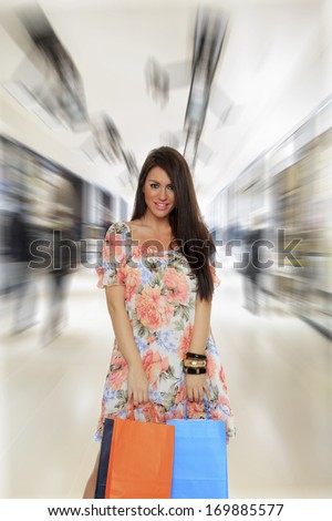 young woman holding shopping at the mall - stock photo