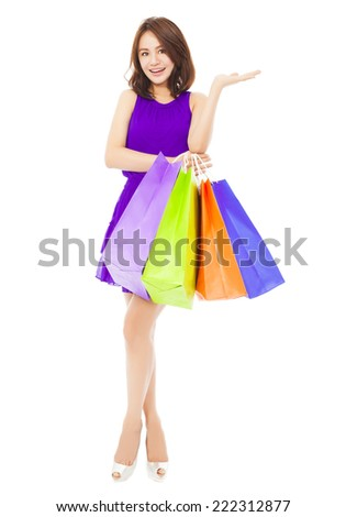 young woman holding shopping bags and hand gesture over white background - stock photo