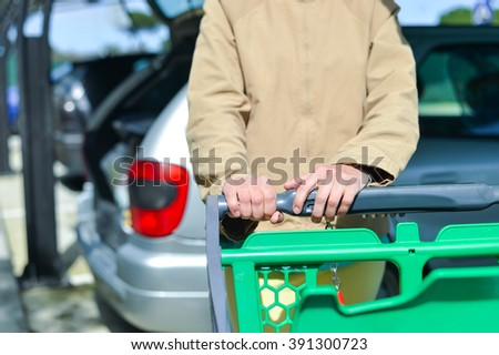 Young woman holding shopping push cart closeup picture of hands with car on background - stock photo