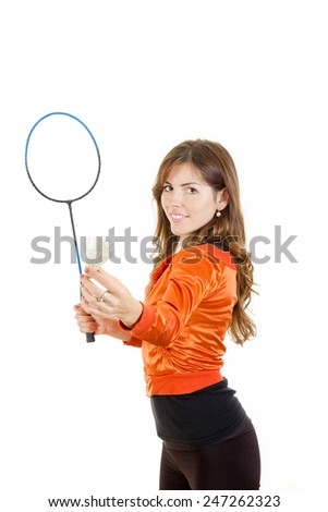 Young woman holding shuttlecock and racket playing badminton smiling - stock photo