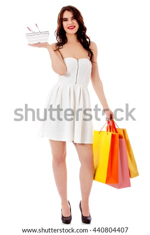 Young woman holding small empty shopping basket and shopping bags - stock photo
