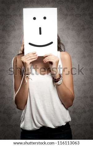 young woman holding smile symbol in front of her face - stock photo