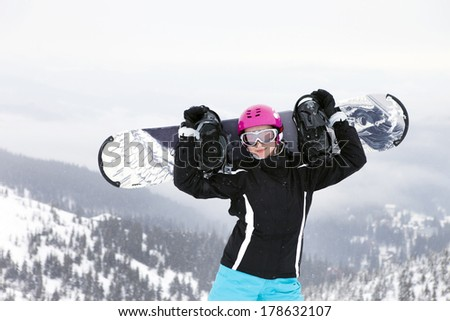 Young woman holding snowboard, she's looking away and smiling, copy space, close-up - stock photo